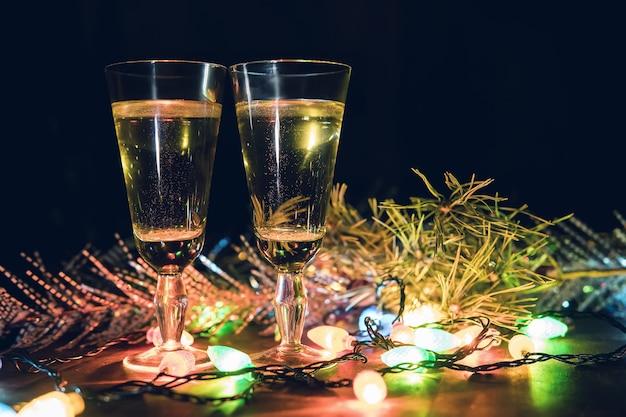 Twee glazen met champagne op een houten tafel versierd met kerstaccessoires om het nieuwe jaar en kerstmis te vieren. romantische avond. de gloed van de slingers