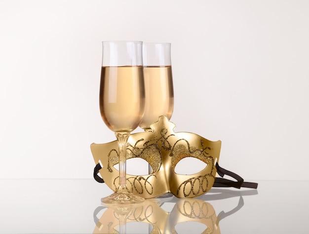 Twee glazen met champagne op een tafel met maskerade masker