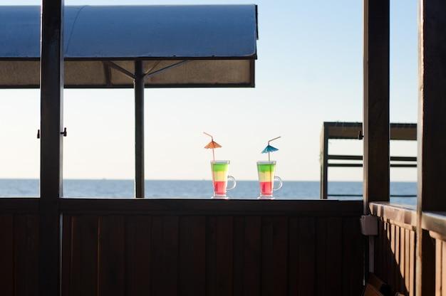 Twee glazen met cocktails op een houten bureau tegen de zee