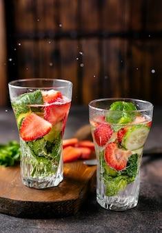 Twee glazen met gegoten water op rustieke achtergrond
