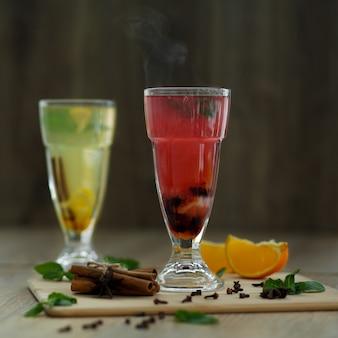 Twee glazen met gekleurde warme dranken waaruit stoom komt. winter warme seizoensgebonden drankjes