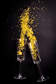 Twee glazen met gele klatergoud op zwart, plat bovenaanzicht