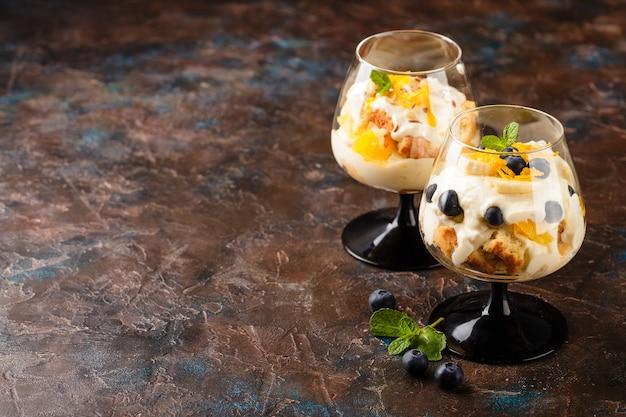 Twee glazen met gezonde zelfgemaakte gelaagde dessert kleinigheid met sinaasappel, bosbes, koekje, yoghurt en muesli. plaats voor tekst