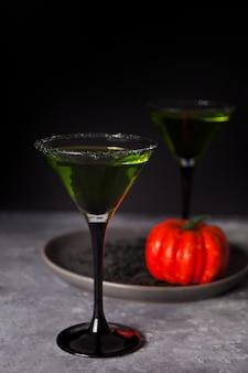 Twee glazen met groene zombiecocktail voor halloween-partij op dark