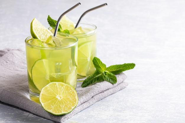 Twee glazen met iced groene matcha thee met limoen, ijs, verse munt en metalen rietjes.