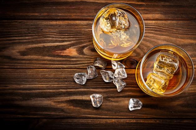 Twee glazen met ijs en whisky (bovenaanzicht)