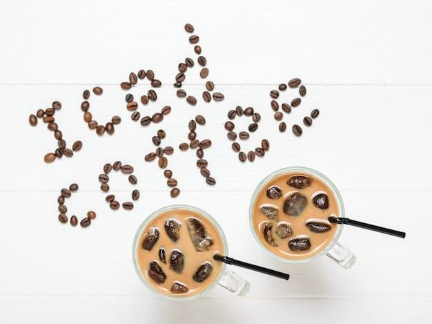 Twee glazen met ijs koffie en cocktail buizen en een inscriptie van ijs koffie op een witte tafel. verfrissende en verkwikkende drank van koffiebonen en melk. het uitzicht vanaf de top. plat liggen.