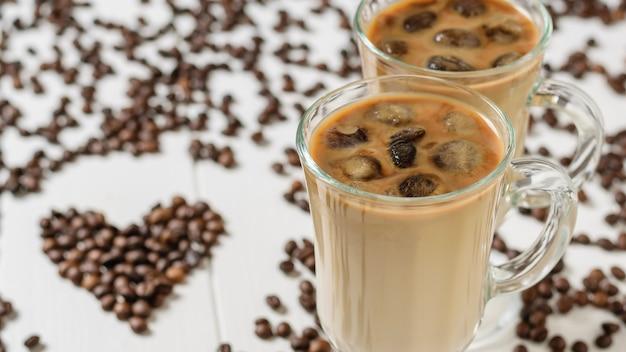 Twee glazen met ijskoffie en cocktailbuizen met harten van koffiebonen.