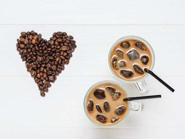 Twee glazen met ijskoffie en cocktailbuizen op de achtergrond van het hart van koffiebonen. verfrissende en verkwikkende drank van koffiebonen en melk. het uitzicht vanaf de top. plat liggen.