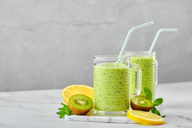 Twee glazen met kiwi en citroen smoothie met munt op marmeren achtergrond en plakjes fruit background