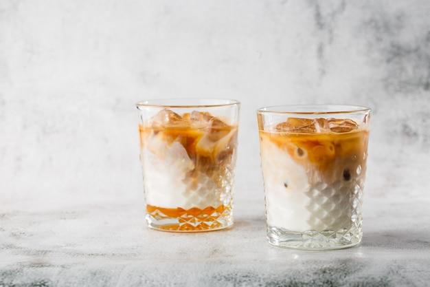 Twee glazen met koude brouwt koffie en melk die op heldere marmeren achtergrond wordt geïsoleerd. bovenaanzicht, kopieer ruimte. reclame voor café-menu. coffeeshop menu. horizontale foto.