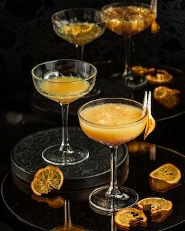 Twee glazen met lange steel van oranje cocktail met pulp