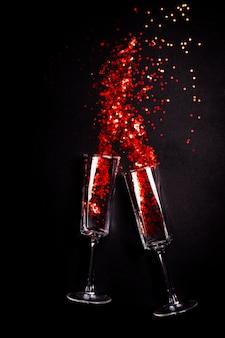 Twee glazen met rode confetti op zwart, plat lag bovenaanzicht
