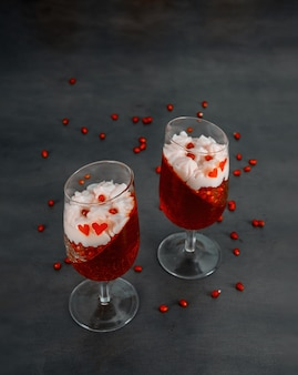Twee glazen met rode gelatine, slagroom en granaatappelzaden bovenop.