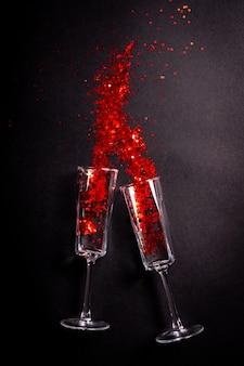 Twee glazen met rode klatergoud op zwart, plat lag bovenaanzicht