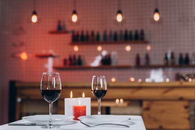Twee glazen met rode wijn en brandende kaarsen op een gedekte lijst in een restaurantclose-up