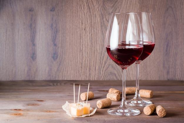 Twee glazen met rode wijn, stukjes kaas en kurk op een houten tafel
