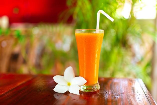 Twee glazen met vers geperst sap en frangipani bloem