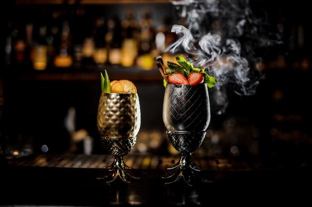 Twee glazen met verse zomercocktails versierd met fruit op de toog