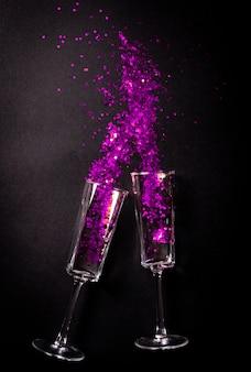 Twee glazen met violet klatergoud op zwart, plat bovenaanzicht