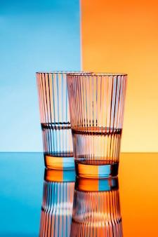 Twee glazen met water over blauwe en oranje muur