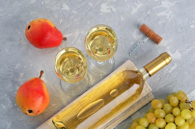 Twee glazen met wijn, fles wijn, rode peren en borstel van druiven op grijze getextureerde tafel. bovenaanzicht. plat leggen.