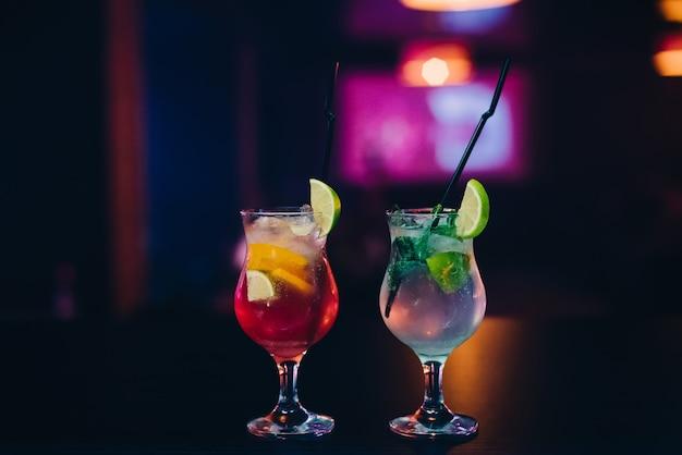 Twee glazen mojito-cocktail met ijs, limoen en munt met buizen