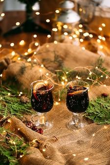 Twee glazen mokken glinsterende wijn met dennentakken