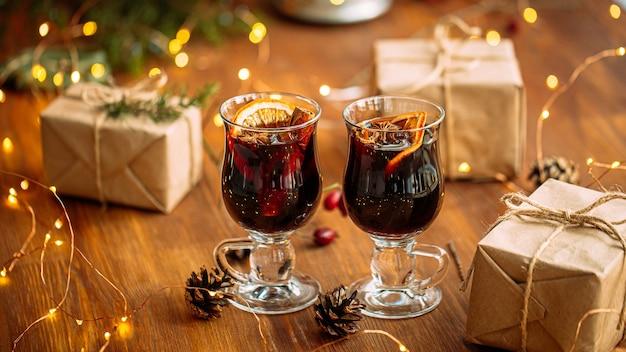 Twee glazen mokken glintwine met ambachtelijke cadeautjes en guirlande lichten op de houten tafel