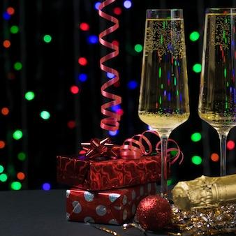 Twee glazen mousserende wijn en kerstcadeaus. concept van kerstmis en nieuwjaar.