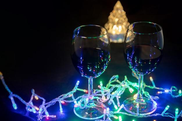 Twee glazen op de achtergrond van een glanzende kerstboom en een veelkleurige slinger op een donkere nacht