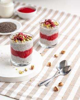 Twee glazen pot chia pudding met framboos, pistache en rode jam op een witte tafel met gestreept tafelkleed.
