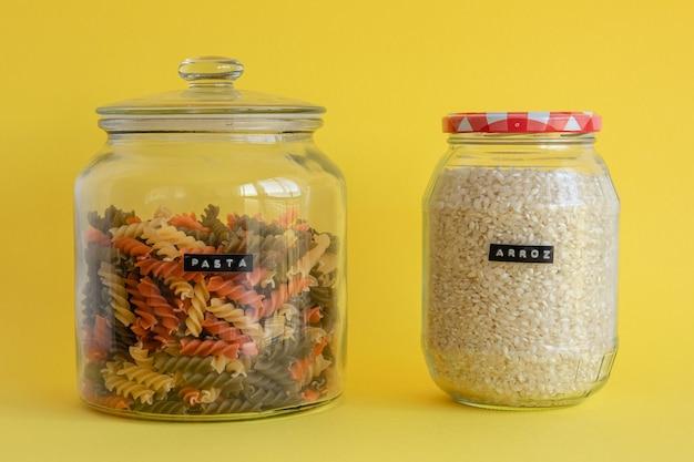 Twee glazen potten gevuld met kleurrijke spiraal pasta en rijst geïsoleerd op gele achtergrond