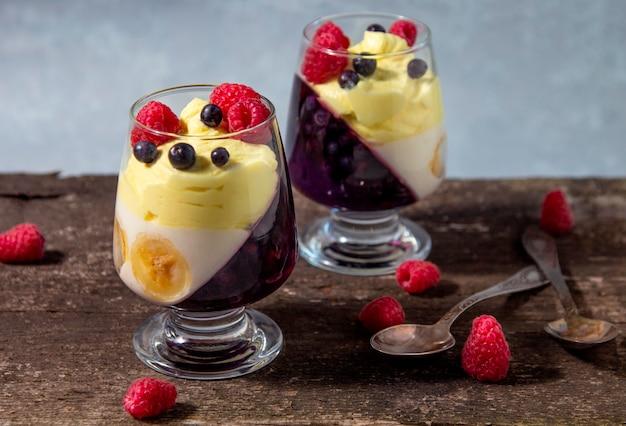 Twee glazen potten met koud dessert (panna cotta, gelei, mousse, pudding) met paarse bosbessen en witte bananenlagen op houten rustieke tafel