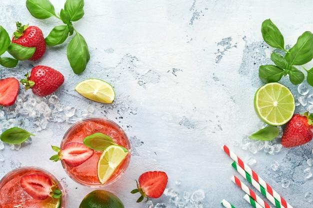 Twee glazen punch en verse ingrediënten voor het maken van limonade, infused detox water of cocktail. aardbeien, limoen, munt, basilicum, ijsblokjes en shaker op grijze steen of betonnen ondergrond. bovenaanzicht.