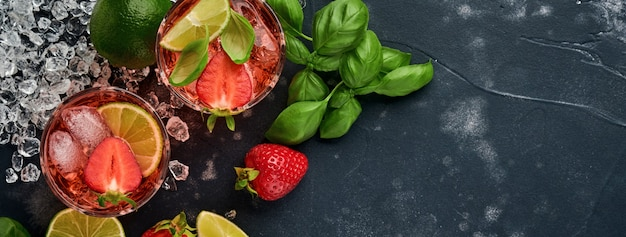 Twee glazen punch en verse ingrediënten voor het maken van limonade, infused detox water of cocktail. aardbeien, limoen, munt, basilicum, ijsblokjes en shaker op zwarte steen of betonnen ondergrond. bovenaanzicht.