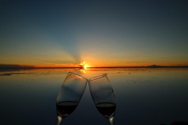 Twee glazen rammelen om te vieren bij de zonsondergang op het spiegeleffect van uyuni salt flats,