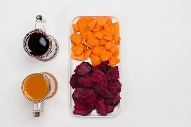 Twee glazen rode biet en wortelsap. gesneden wortelen en bieten in plaat. plat leggen. witte achtergrond. kopieer ruimte