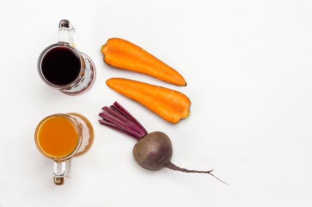 Twee glazen rode biet en wortelsap. wortelgroenten van bieten en wortelen in twee helften gesneden. plat leggen. witte achtergrond. kopieer ruimte
