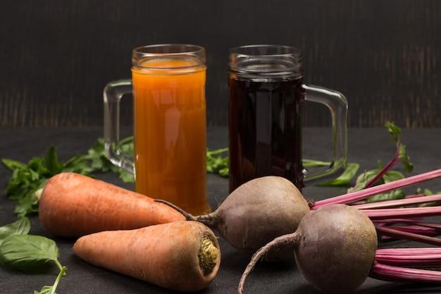 Twee glazen rode biet en wortelsap. wortelgroenten van bieten en wortelen, peterselie en basilicum. bovenaanzicht. zwarte achtergrond