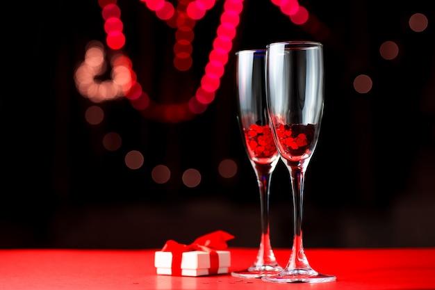 Twee glazen rode harten. naast hen ligt een geschenk. valentijnsdag concept