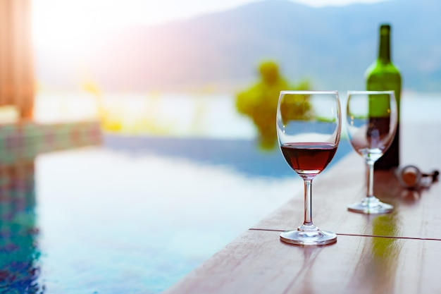 Twee glazen rode wijn bij het zwembad met een spectaculair uitzicht op de zee