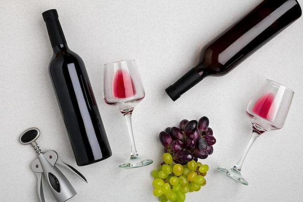 Twee glazen rode wijn en druiven. twee flessen wijn en een kurkentrekker. bovenaanzicht met kopieerruimte