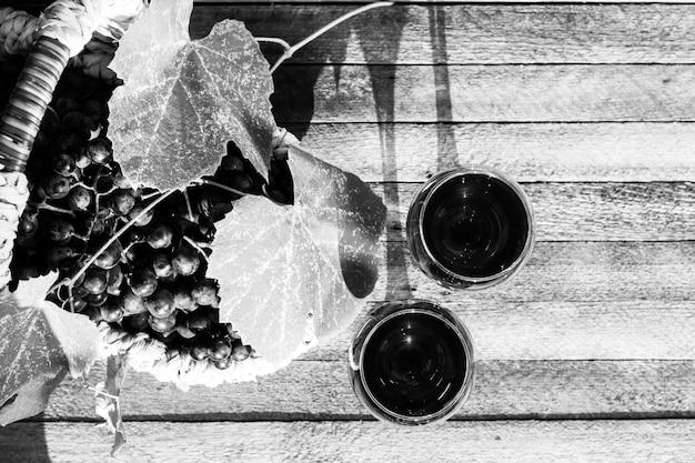 Twee glazen rode wijn en een mand met druiven op een houten achtergrond