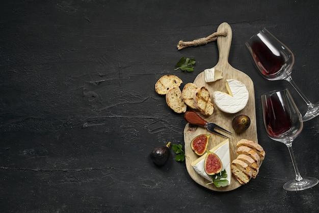 Twee glazen rode wijn en een smakelijk kaasplateau met fruit en geroosterd brood op een houten keukenplaat op de zwarte stenen achtergrond, bovenaanzicht, kopieerruimte. gastronomisch eten en drinken.