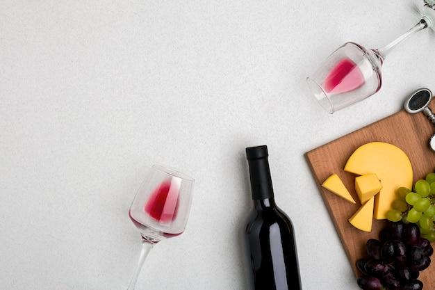 Twee glazen rode wijn kaas en druiven bovenaanzicht