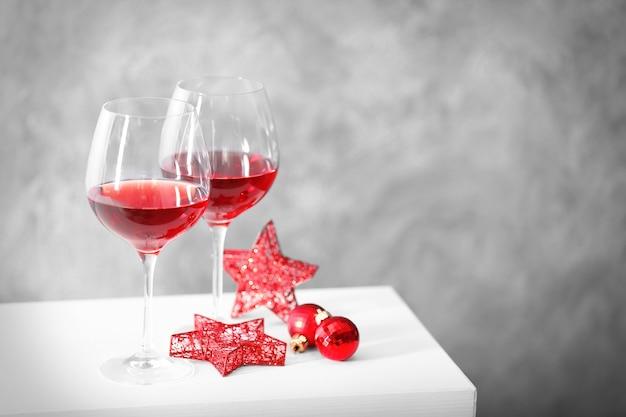 Twee glazen rode wijn met kerstaccessoires op grijze muur