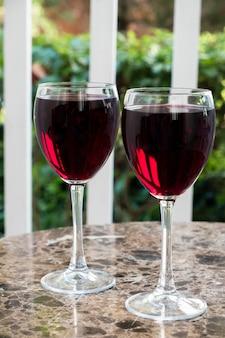Twee glazen rode wijn op een tafel. buitenshuis