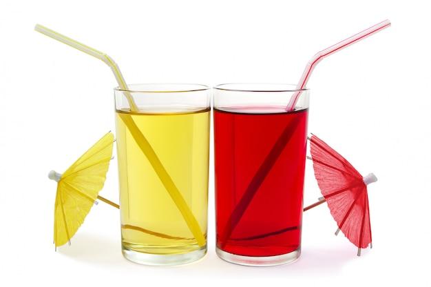 Twee glazen rood en geel vruchtensap op een wit