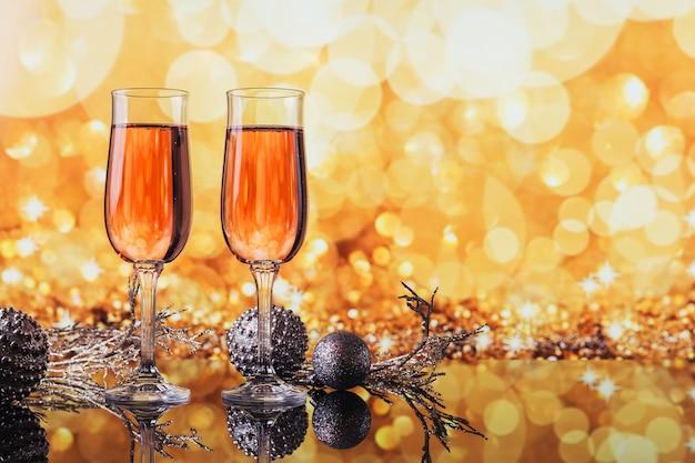 Twee glazen roze champagne en decoratie van kerstmis of nieuwjaar met een gouden licht bokeh